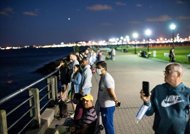 Pessoas mascaradas assistem a fogos de artifício no porto da cidade de Nova York, em meio à vacinação contra a doença do novo coronavírus (COVID-19), na Cidade de Nova Jersey, Nova Jersey, EUA, 15 de junho de 2021