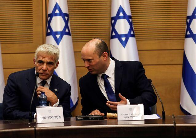 Naftali Bennett, primeiro-ministro de Israel (à direita), e Yair Lapid, ministro das Relações Exteriores de Israel, participam de sua primeira reunião de gabinete no Knesset, o Parlamento israelense, em Jerusalém, 13 de junho de 2021