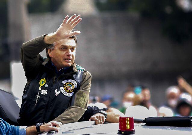 Presidente Jair Bolsonaro acena enquanto lidera motociata com simpatizantes em São Paulo, Brasil, em 12 de junho de 2021
