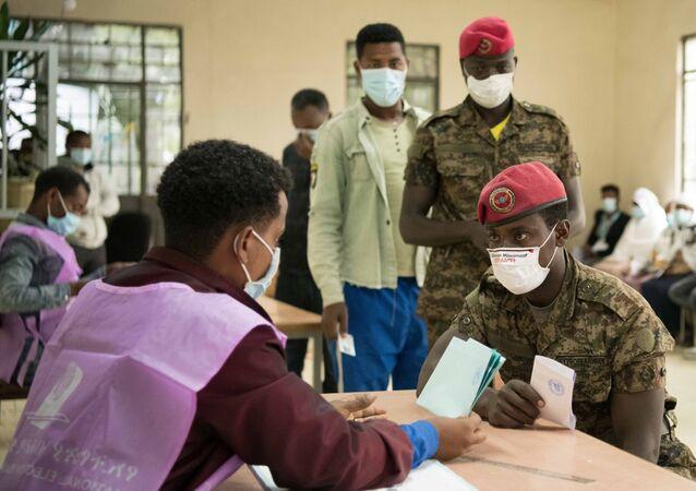 Funcionário confere dados de um membro da segurança etíope durante as eleições parlamentares e regionais em Adis Abeba, Etiópia, 21 de junho de 2021