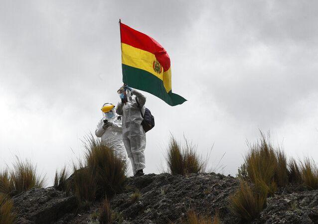 Profissionais de saúde com equipamentos de proteção completos para conter a propagação do novo coronavírus hasteam bandeira boliviana nos arredores de Choquecota, Bolívia. Foto de arquivo