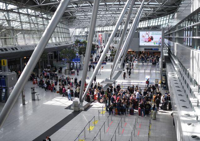Viajantes com máscaras faciais fazem fila nos balcões de check-in no aeroporto de Dusseldorf, Alemanha, 2 de julho de 2021