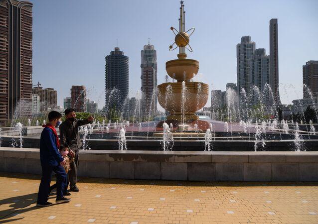 Pessoas caminham diante de fonte na praça da Casa de Cultura em Pyongyang, Coreia do Norte, 25 de abril de 2021
