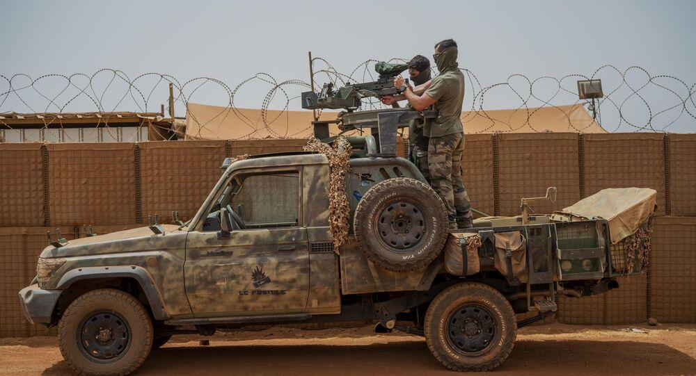 Soldados da força francesa da operação Barkhane montam uma metralhadora em uma picape camuflada enquanto trabalhadores do Mali passam antes de partir em uma missão de sua base em Gao, Mali, 7 de junho de 2021