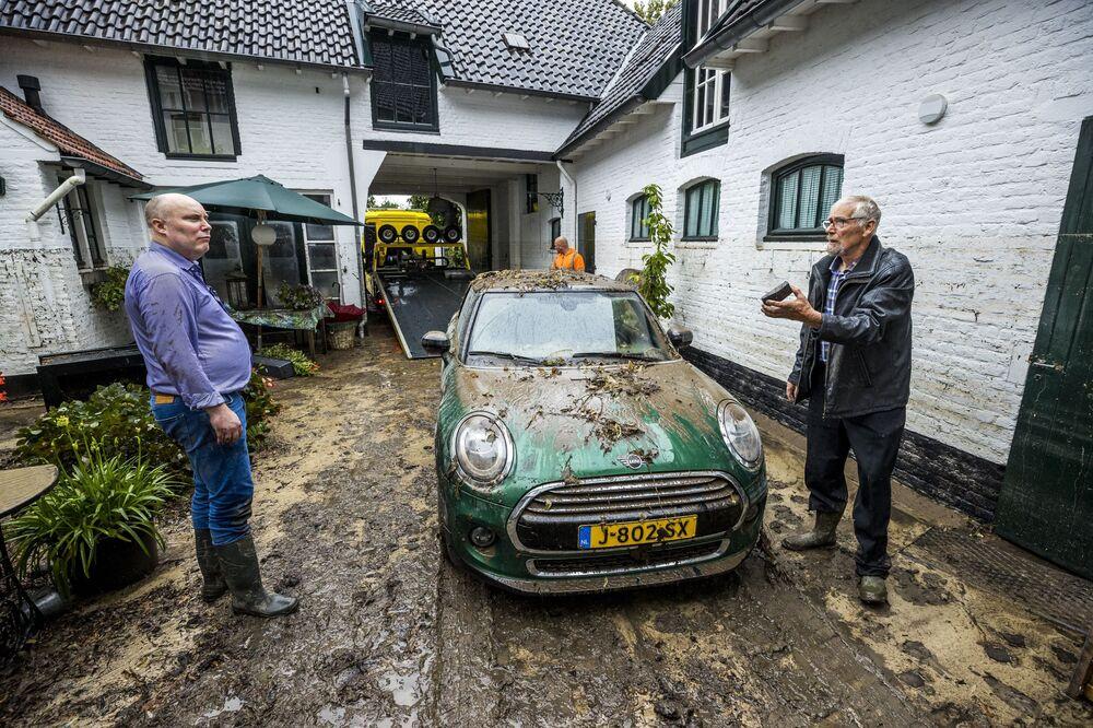 Pessoas em pátio coberto de lama após chuvas fortes em Heerlen, Países Baixos