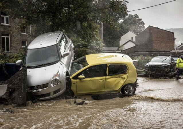 Carros danificados em rua inundada em Mery, na Bélgica