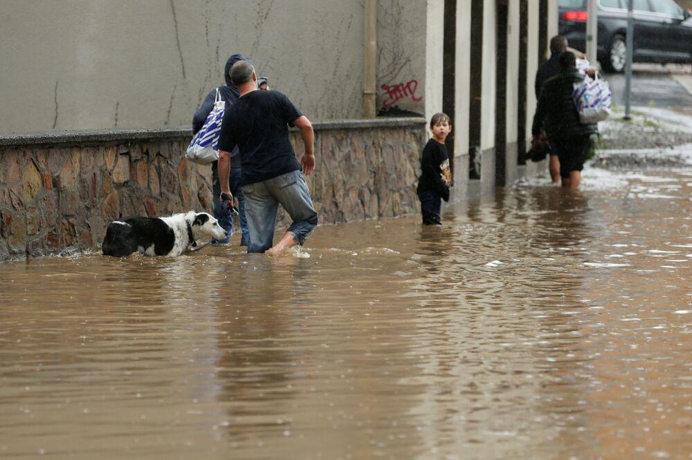 Pessoas caminham por rua inundada após chuvas torrenciais em Hagen, Alemanha