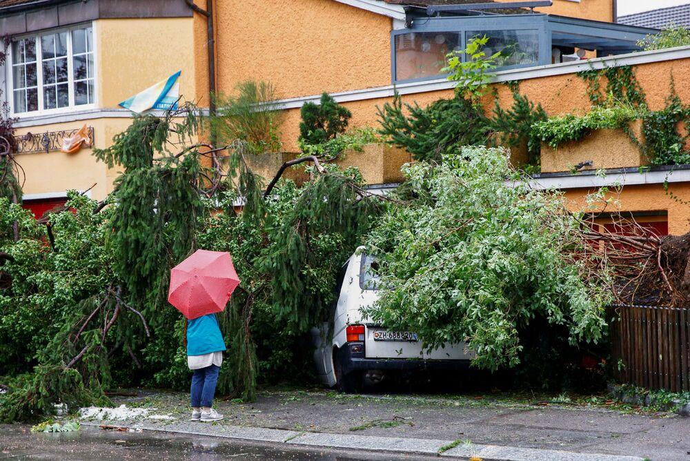 Mulher diante de van danificada por queda de árvore durante tempestade e chuvas fortes em Zurique, Suíça