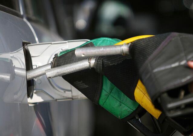 Frentista, com bomba de combustível, abastece automóvel, em posto de gasolina de São Paulo, Brasil. Foto de arquivo