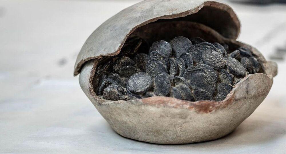 Jarro pesado de cerâmica contendo centenas de moedas milenares
