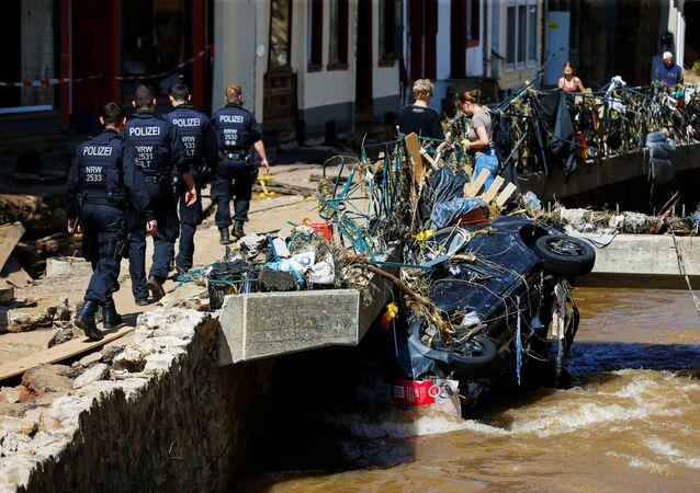 Policiais passam por carro danificado em uma área afetada por inundações causadas por fortes chuvas em Bad Muenstereifel, Alemanha, 18 de julho de 2021