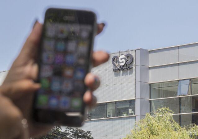 Mulher usa seu iPhone em frente ao prédio que abriga o grupo israelense NSO, em Herzliya, próximo a Tel Aviv. Foto de arquivo