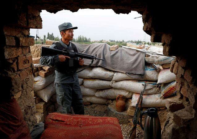 Um policial afegão vigia o posto de controle nos arredores de Cabul, Afeganistão, em 13 de julho de 2021