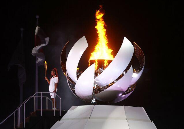 Naomi Osaka do Japão segura a tocha olímpica após acender a pira olímpica na cerimônia de abertura