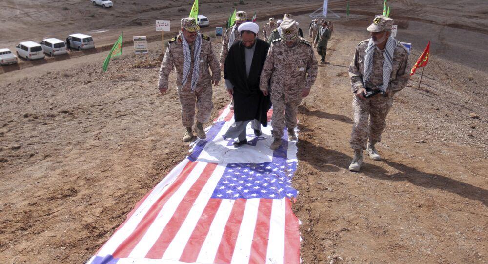 Membros do IRGC e um clérigo caminham sobre representações de bandeiras de Israel e EUA