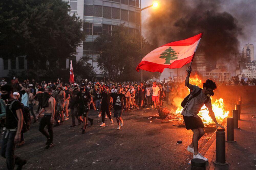 Manifestante segura bandeira libanesa em meio a confrontos com forças de segurança em Beirute, no Líbano, 4 de agosto de 2021