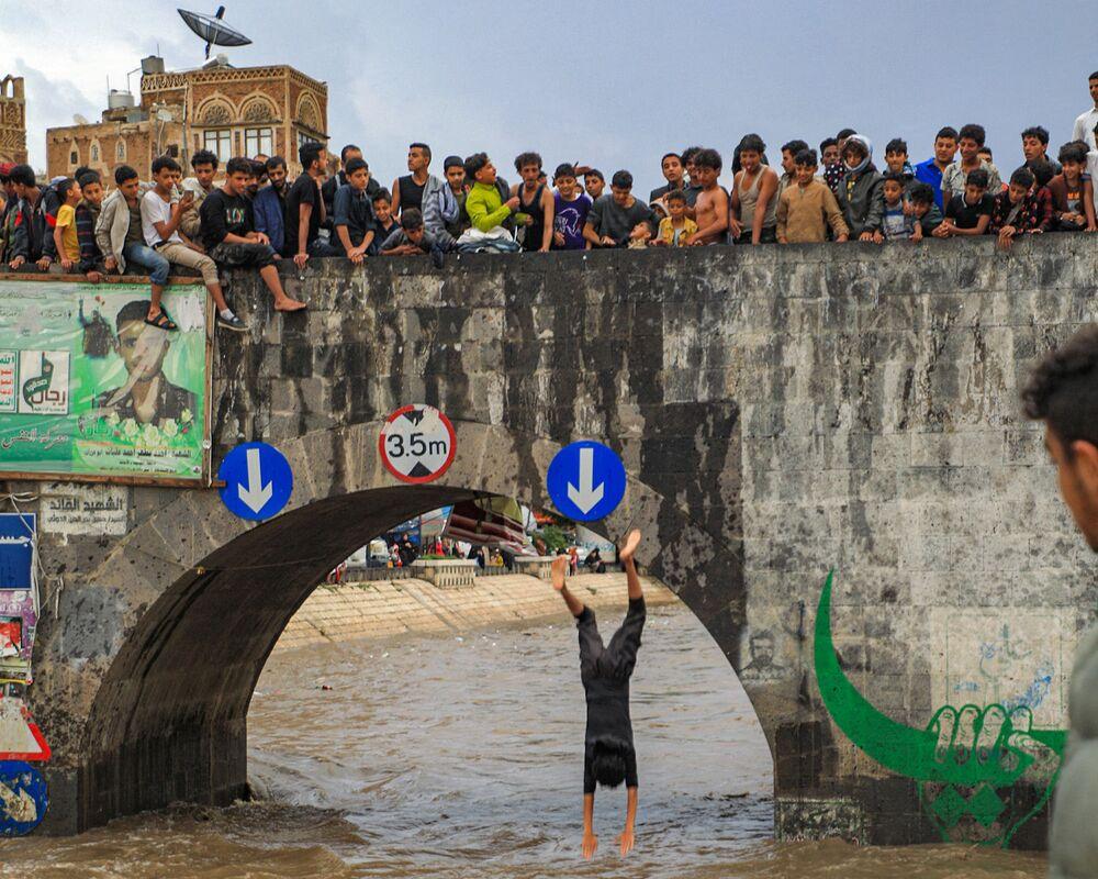 Jovens observam homem saltando de uma ponte na capital do Iêmen, Sanaa, 3 de agosto de 2021