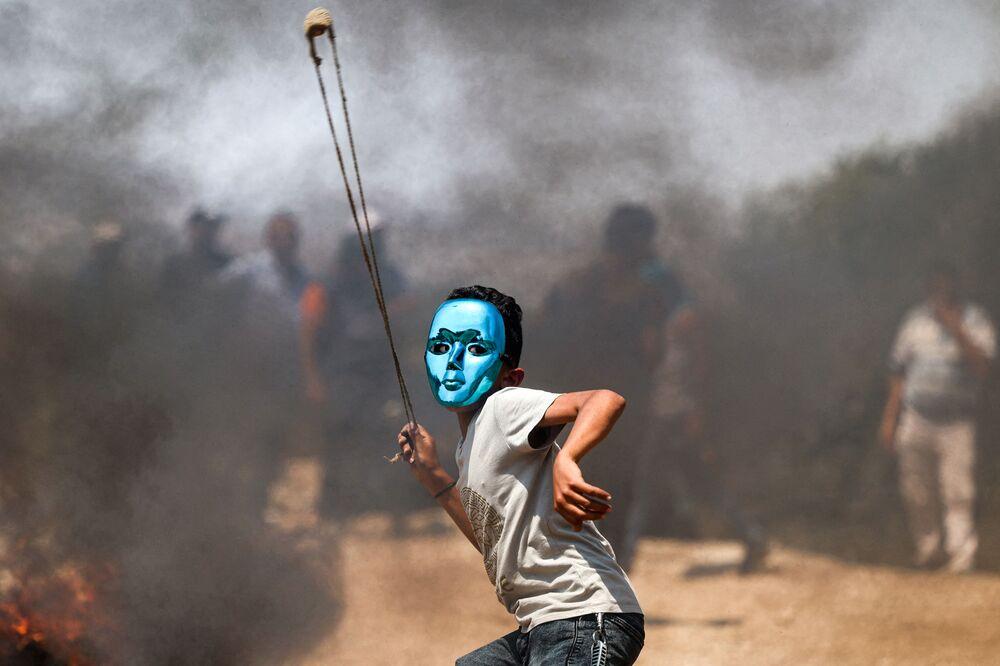 Criança palestina atira estilingue em soldados israelenses na cidade de Beita, no norte da Cisjordânia, 30 de julho de 2021