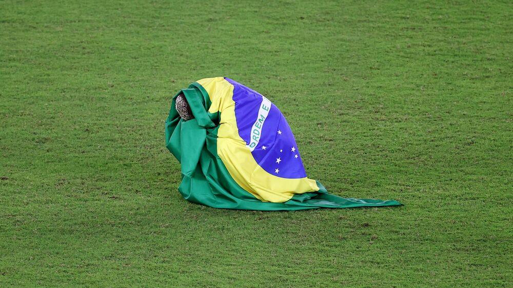 Jogador Richarlison chora de emoção abraçado à bandeira do Brasil, após seleção olímpica vencer a Espanha na final de futebol nas Olimpíadas, 7 de agosto de 2021