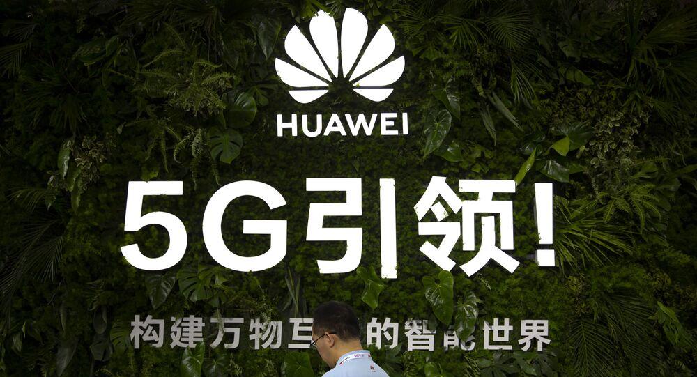 Um membro da equipe usa seu smartphone em um display para serviços 5G da empresa de tecnologia chinesa Huawei na PT Expo em Pequim, quinta-feira, 31 de outubro de 2019