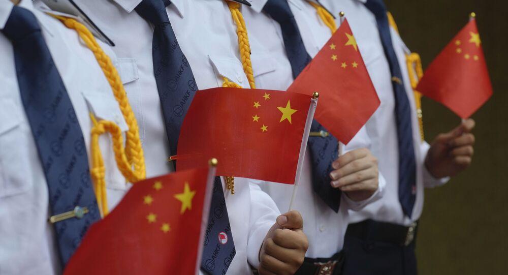 Os alunos seguram as bandeiras nacionais chinesas durante uma cerimônia de hasteamento da bandeira para marcar o 24º aniversário da transferência de Hong Kong para a China, 1º de julho de 2021