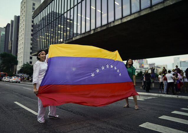 Manifestantes antigovernamentais venezuelanos bloqueiam carros com sua bandeira nacional em São Paulo, Brasil, 23 de janeiro de 2019