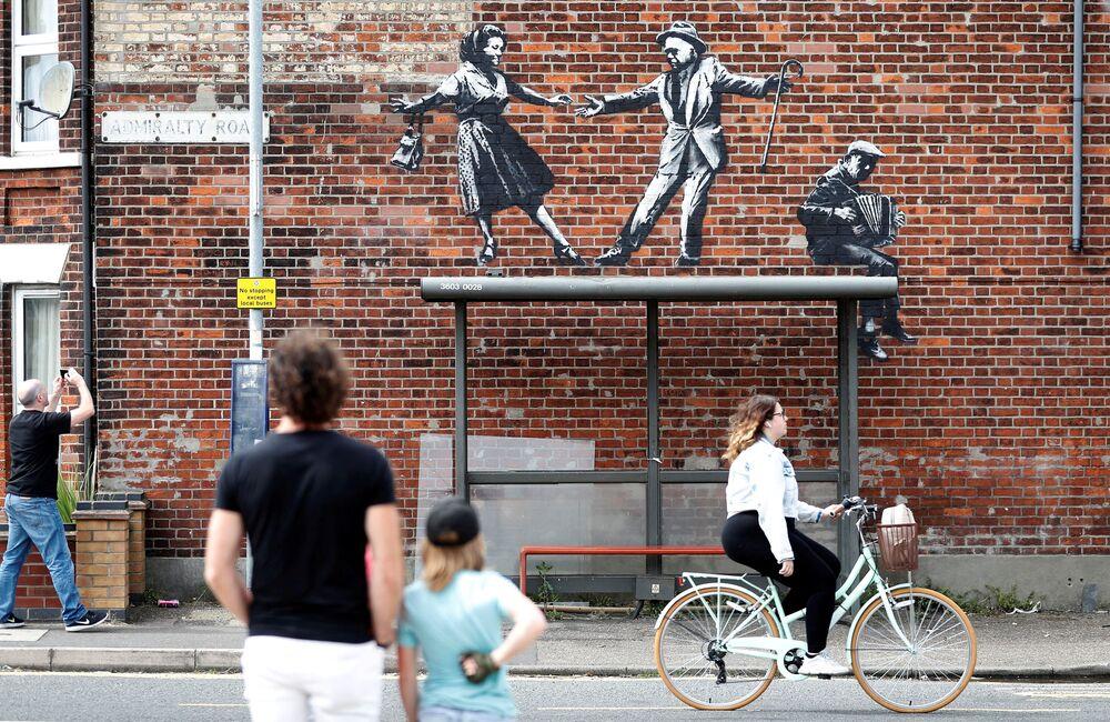 Em Great Yarmouth, no Reino Unido, pessoas param para observar arte urbana, provavelmente da autoria de Banksy, 8 de agosto de 2021