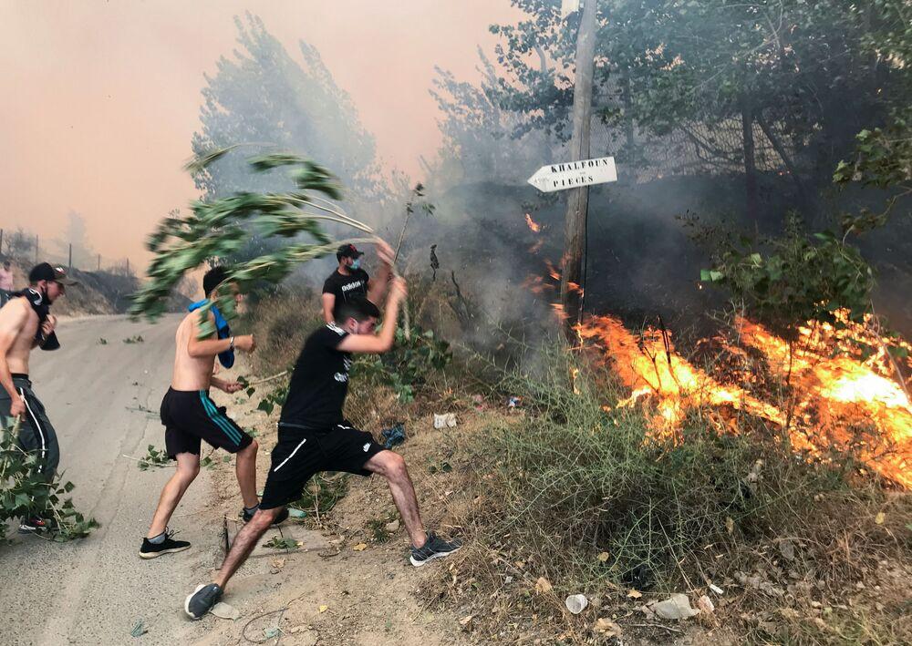 Várias pessoas tentam apagar um incêndio em uma montanha da província de Tizi Ouzou, a leste de Argel, na Argélia, 10 de agosto de 2021