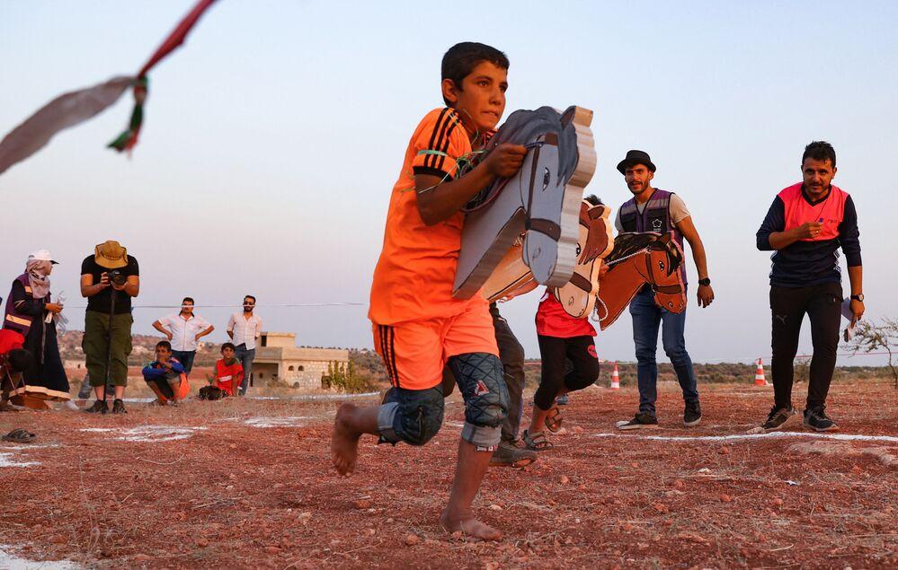 Crianças refugiadas sírias brincam durante os Campos Olímpicos 2020 na cidade de Foua, o último grande bastião rebelde da região de Idlib, 7 de agosto de 2021
