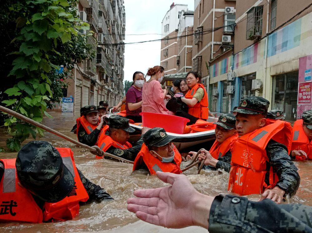 Polícia paramilitar evacua áreas isoladas pelas cheias após chuvas fortes na cidade de Suizhou, na província chinesa de Hubei, 12 de agosto de 2021