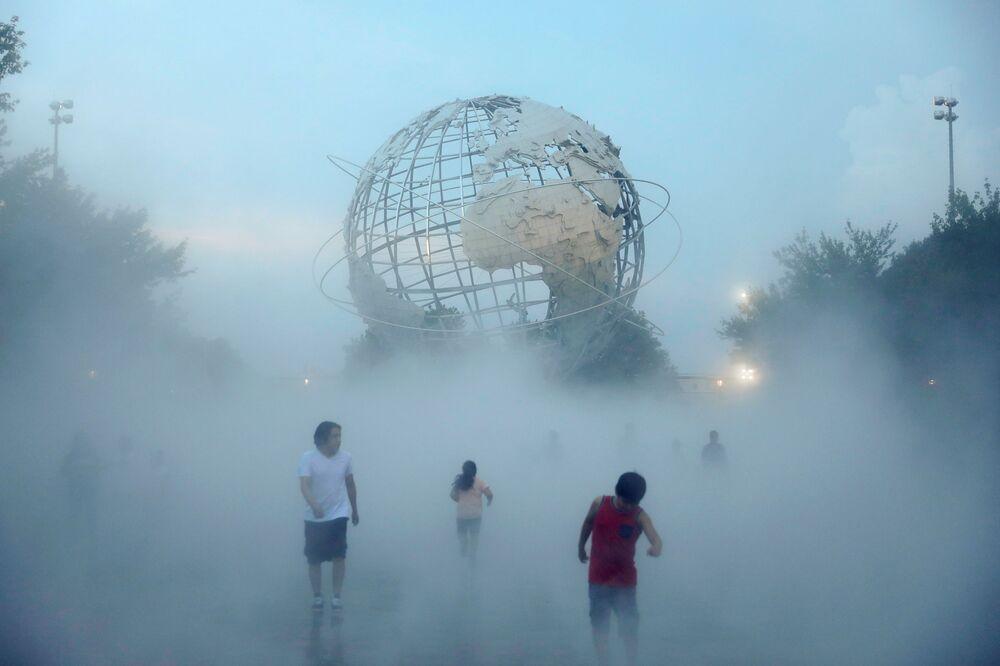 Pessoas no jardim em frente à Unisfera em Flushing Meadows-Corona Park, enquanto uma onda de calor atinge a região de Queens, em Nova York, nos EUA, 11 de agosto de 2021