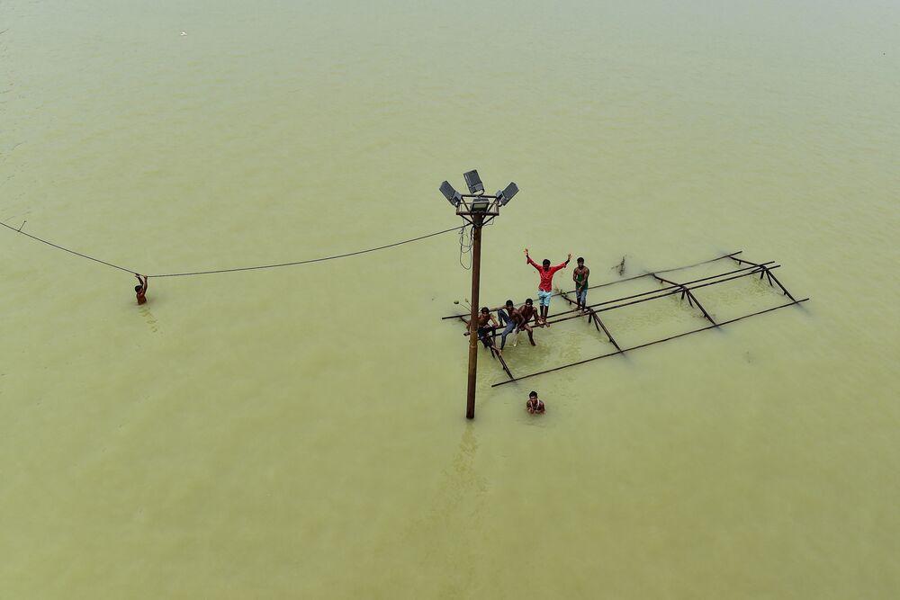 Alguns garotos, juntamente com barqueiros locais, brincam no topo de uma estrutura submersa em Daraganj Ghat, uma das margens inundadas do rio Ganges em Allahabad, na Índia, 8 de agosto de 2021