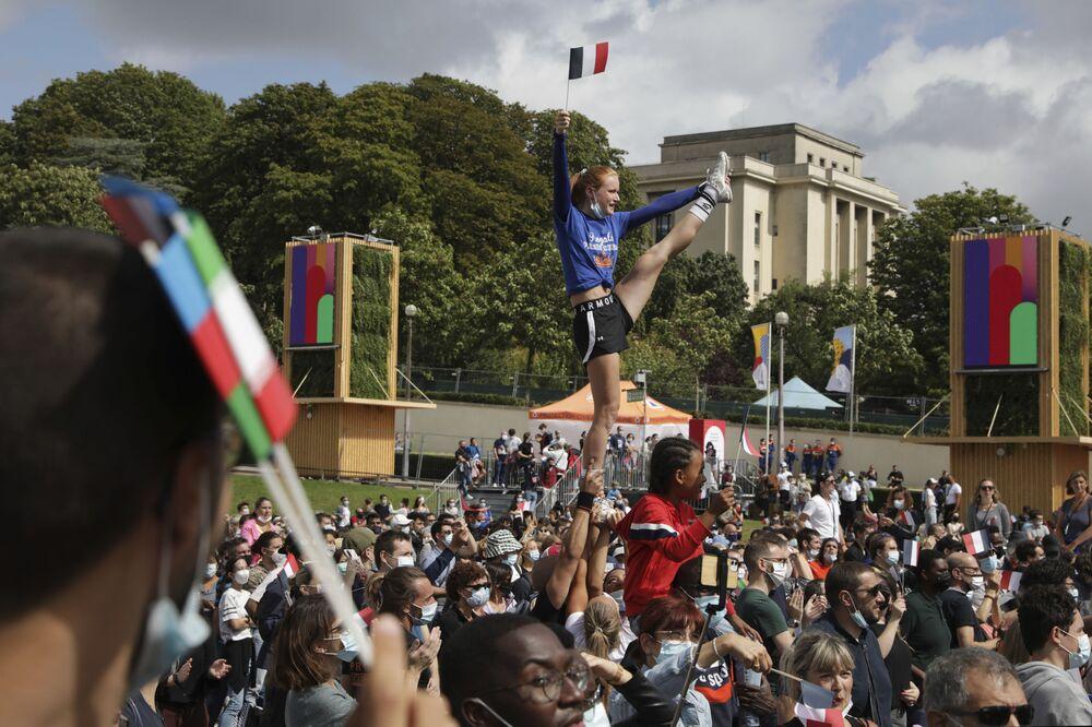 Uma mulher segura a bandeira francesa enquanto mostra suas acrobacias na zona de fãs dos Jogos Olímpicos na capital francesa, Paris, 8 de agosto de 2021
