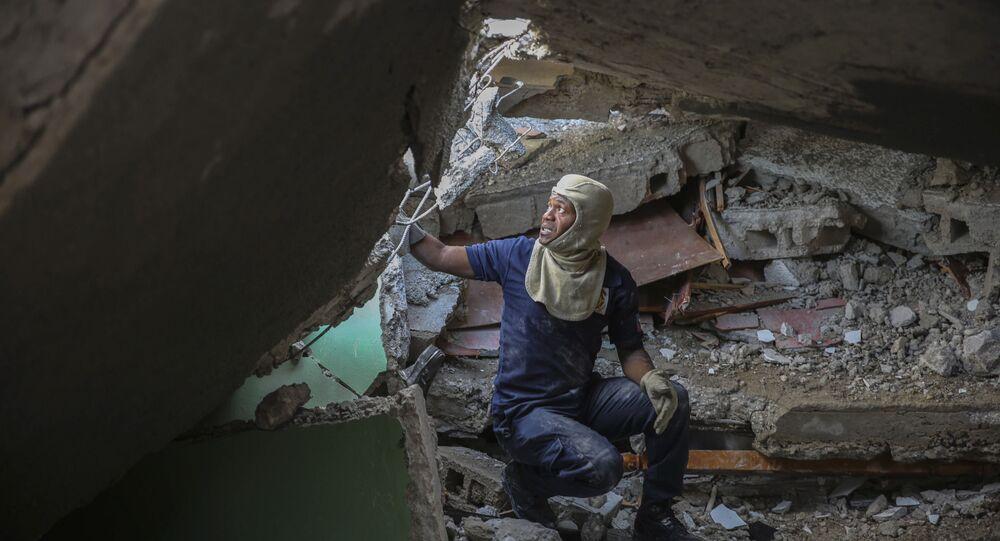 Bombeiro procura sobreviventes no prédio destruído durante terremoto no Haiti, 15 de agosto de 2021