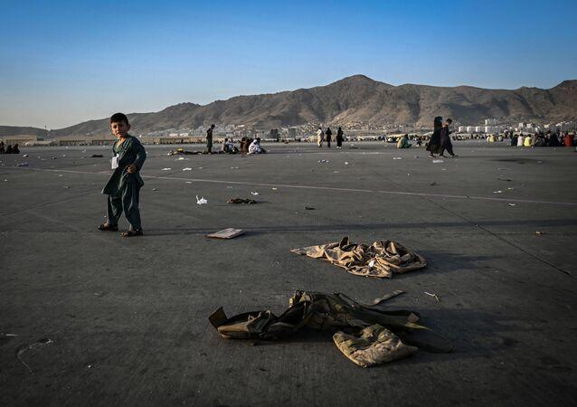 Criança afegã caminha perto de uniformes militares no aeroporto de Cabul, em 16 de agosto de 2021
