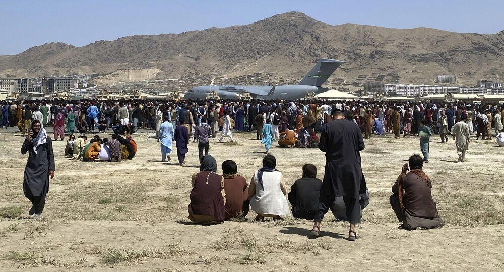Centenas de pessoas se reúnem perto de um avião de transporte C-17 da Força Aérea dos EUA em um perímetro no aeroporto internacional de Cabul, Afeganistão, 16 de agosto de 2021