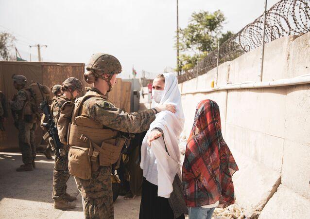 Fuzileira naval dos EUA verifica dois civis durante processo de evacuação no Aeroporto Internacional Hamid Karzai, Cabul, Afeganistão, 18 de agosto de 2021