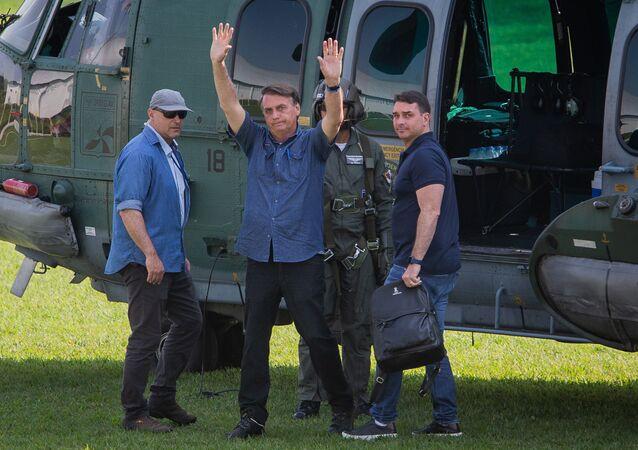 O presidente Jair Bolsonaro, junto com seu filho Flávio Bolsonaro, ao deixar a cidade de Eldorado, interior do estado de São Paulo., 21 de agosto de 2021