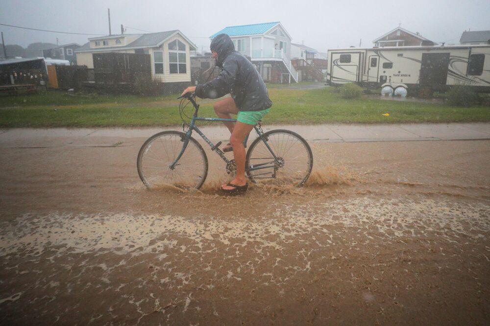 Ciclista em rua inundada enquanto tempestade tropical Henri se aproxima de South Kingstown, Rhode Island, EUA, 22 de agosto de 2021