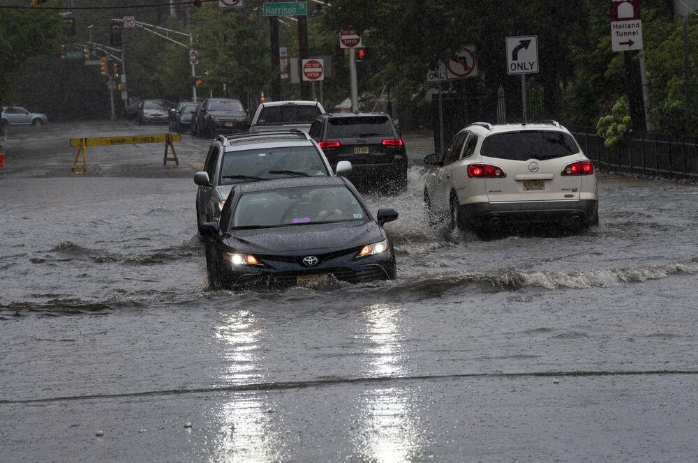 Carros passam por rua inundada após tempestade tropical Henri, em Hoboken, Rhode Island, EUA, 22 de agosto de 2021
