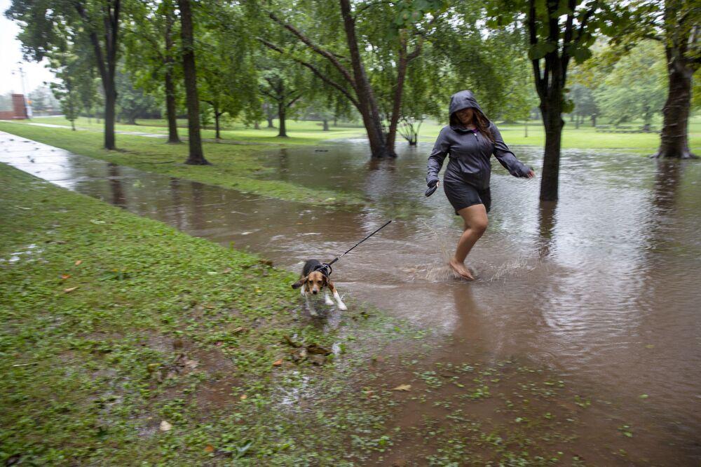 Mulher passeia com cachorro por caminho inundado devido à tempestade tropical Henri em Hartford, Connecticut, EUA, 22 de agosto de 2021