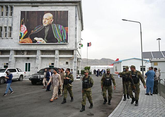 Pessoal de segurança passa ao lado de poster do ex-presidente afegão Hamid Karzai no aeroporto de Cabul em seu nome, 16 de julho de 2021