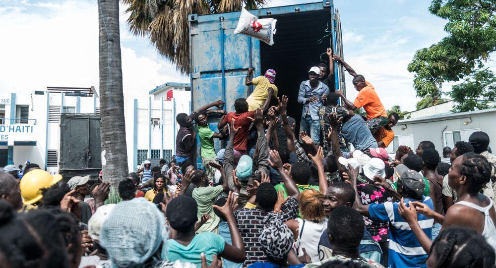 Homem joga saco de arroz para multidão durante distribuição de alimentos e água entre vítimas do terremoto em Les Cayes, Haiti