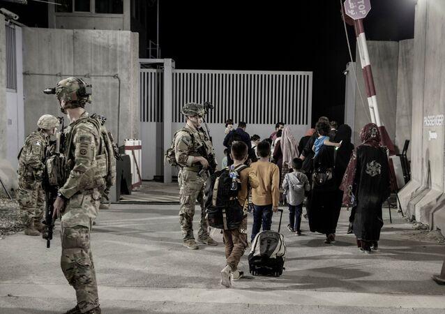 Soldados dos EUA escoltam civis durante evacuação no Aeroporto Internacional Hamid Karzai Cabul, Afeganistão, 25 de agosto de 2021