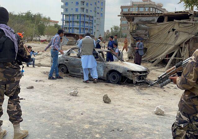 Afegãos tiram fotos do veículo a partir do qual os foguetes foram lançados, Cabul, Afeganistão, 30 de agosto de 2021