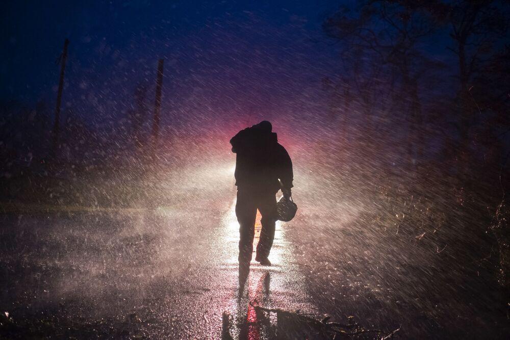 Chefe de bombeiros caminha em chuva pesada enquanto os bombeiros cortam árvores na estrada em Bourg, Louisiana, durante o furacão Ida, 29 de agosto de 2021