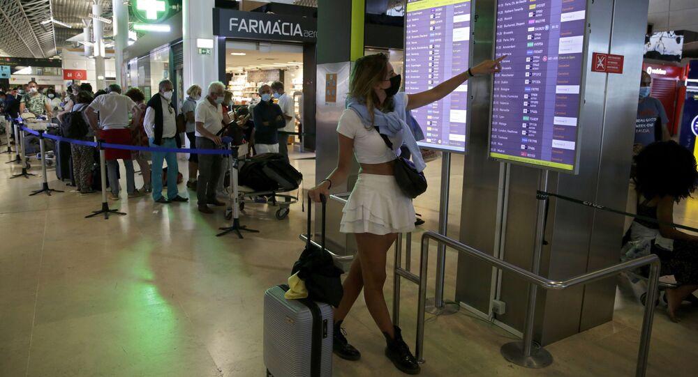 Passageira confere o painel de voos no Aeroporto de Lisboa, em 17 de julho de 2021