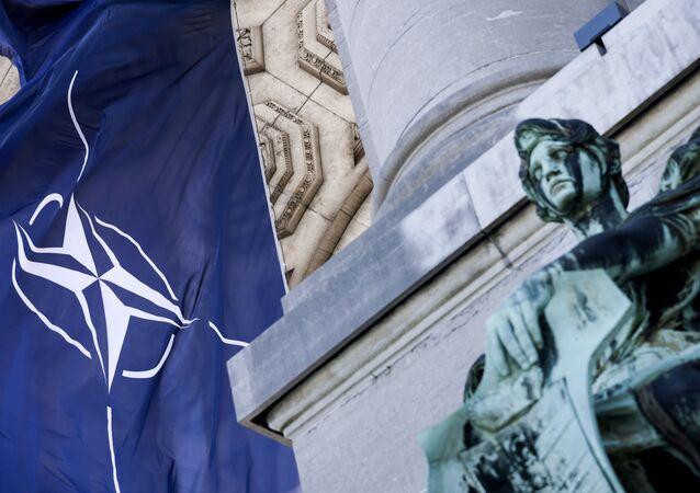 Bandeira da OTAN ao lado de estátua no Parque do Cinquentenário, Bruxelas, Bélgica, 13 de junho de 2021