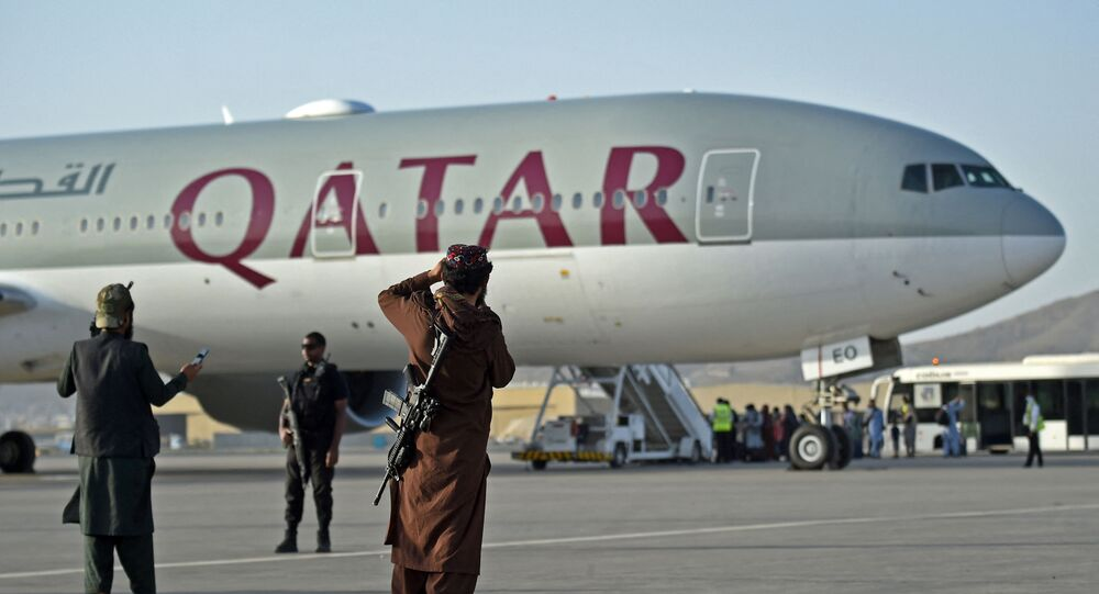 Segurança do Catar e militantes do Talibã fazem guarda enquanto os passageiros embarcam no avião da Qatar Airways no aeroporto de Cabul, 9 de setembro de 2021