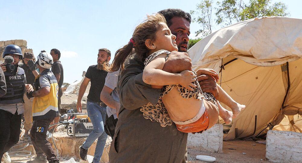 Homem carrega garota, ferida durante bombardeio de campo de refugiados no norte da Síria, 7 de setembro de 2021